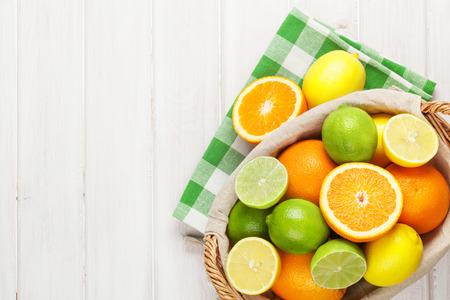 Zitrusfrüchte im Korb. Orangen, Limetten und Zitronen. Über weißen Holztisch Hintergrund mit Kopie Raum