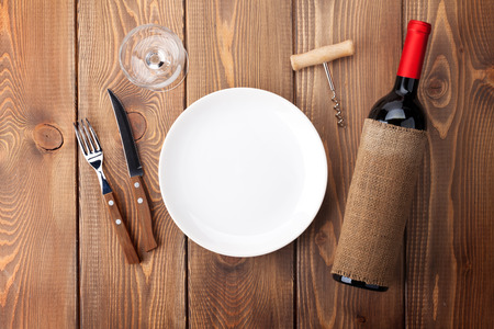 empty: Table setting with empty plate, wine glass and red wine bottle. Top view over rustic wooden table background