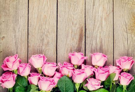 Růžové růže kytice přes dřevěný stůl. Pohled shora s kopií vesmíru. Tónovaný