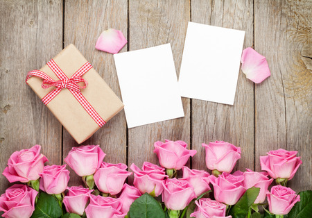 Photo frames, gift box and pink roses over wooden table. Top view