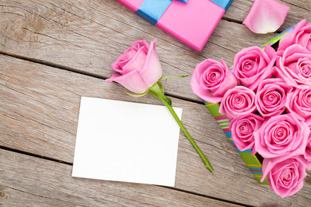 romantic picture: Valentines day greeting card or photo frame and gift box full of pink roses over wooden table. Top view