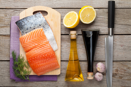 Salmon, spices and condiments on wooden table. Top view photo