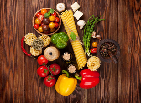 Italian food cooking ingredients. Pasta, vegetables, spices. Top view photo