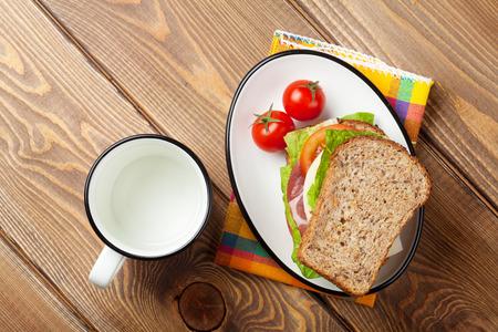 bocadillo: Sandwich con ensalada, jamón, queso y tomates en mesa de madera. Vista superior