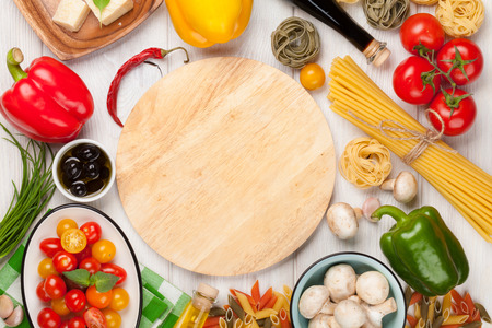 Italian food cooking ingredients. Pasta, vegetables, spices. Top view with cutting board for copy space