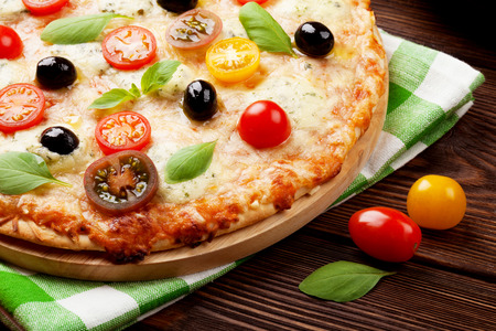Italian pizza with cheese, tomatoes, olives and basil on wooden table photo