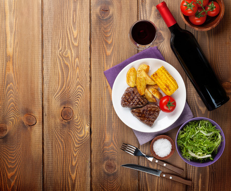 grilled potato: Steak with grilled potato, corn, salad and red wine over wooden table. Top view with copy space