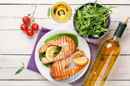 Grilled salmon and white wine on wooden table. Top view photo