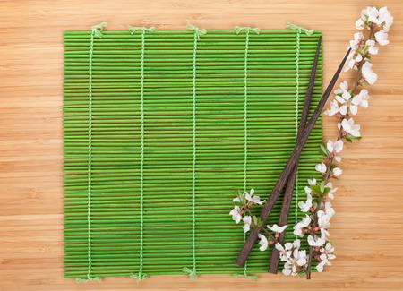 chop stick: Chopsticks and sakura branch over bamboo mat with copy space
