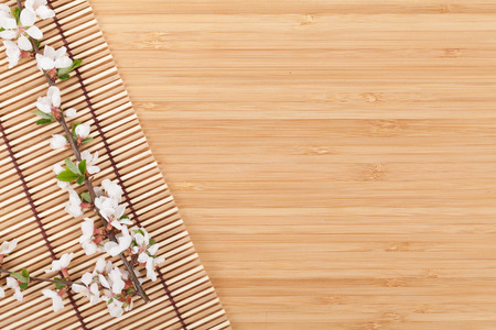 Sakura branch over bamboo mat with copy space