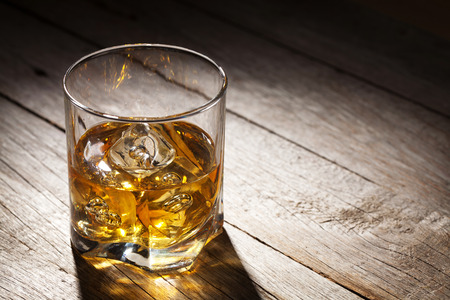 shot glass: Glass of whiskey with ice on wooden table background with copy space