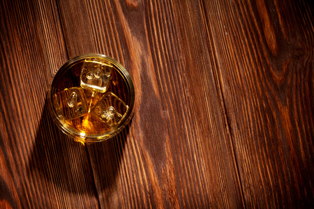Glass of whiskey with ice on wooden table background. Top view with copy space photo