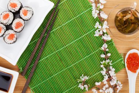 Sushi maki set, green tea and sakura branch over bamboo table with copy space photo