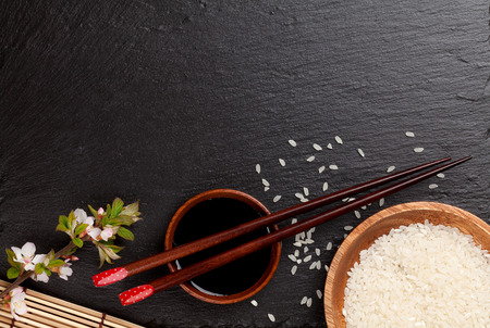 cuisine: Japanese sushi chopsticks over soy sauce bowl, rice and sakura blossom on black stone background. Top view with copy space