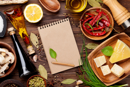 Various spices on wooden background. Top view with notepad for copy space photo