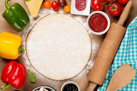 cooking: Ingredientes para cocinar la pizza. Masa, verduras y especias. Vista superior con espacio de copia