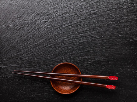 sauce bowl: Japanese sushi chopsticks over soy sauce bowl on black stone background. Top view with copy space