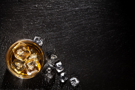 Glass of whiskey with ice on black stone table. Top view with copy space