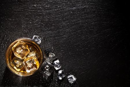 barra de bar: Vidrio de whisky con hielo en mesa de piedra negro. Vista superior con espacio de copia