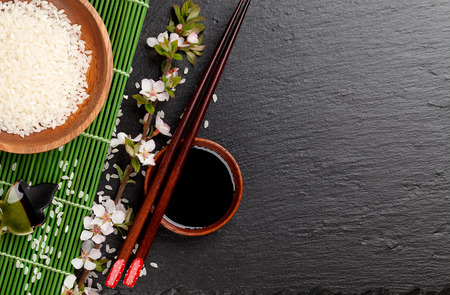 sauce bowl: Japanese sushi chopsticks over soy sauce bowl, rice and sakura blossom on black stone background. Top view with copy space