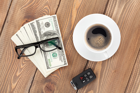 computer key: Money cash, glasses, car remote and coffee cup on wooden table