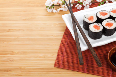 Sushi maki set and sakura branch over bamboo table with copy space