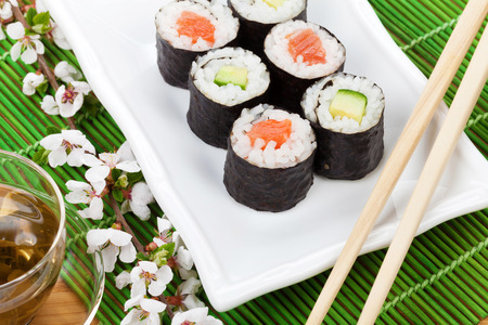 sushi: Sushi maki set, green tea and sakura branch over bamboo table