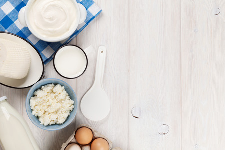 yogur: Productos lácteos en la mesa de madera. Crema agria, leche, queso, huevos y yogur. Vista superior con espacio de copia