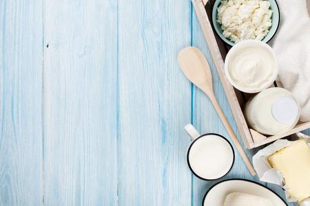 Zuivelproducten op houten tafel. Zure room, melk, kaas, yoghurt en boter. Bovenaanzicht met een kopie ruimte Stockfoto