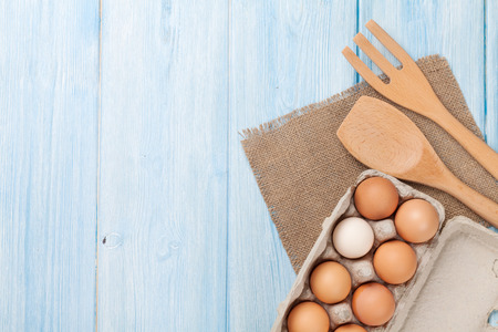 white eggs: Cardboard egg box on wooden table. Top view with copy space Stock Photo