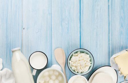 mleko: Produkty mleczne na drewnianym stole. Kwaśna śmietana, mleko, sery, jogurty i masło. Widok z góry z miejsca na kopię