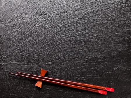 japones bambu: Palillos de sushi japonés sobre negro fondo de piedra. Vista superior con espacio de copia