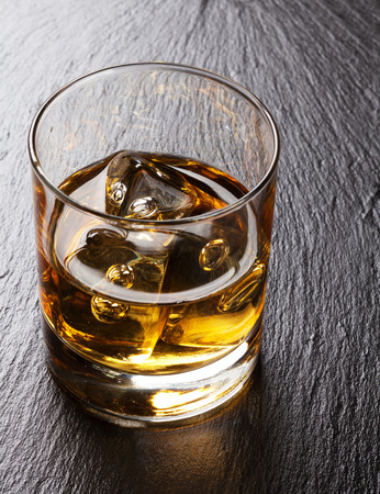 scotch: Glass of scotch whiskey with ice on black stone table Stock Photo