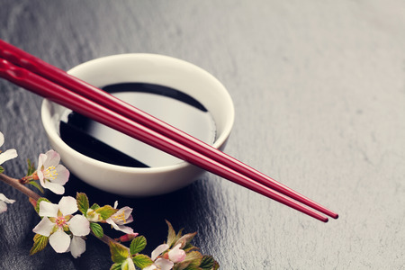 sauce bowl: Japanese sushi chopsticks, soy sauce bowl and sakura blossom on black stone background. Top view with copy space. Toned