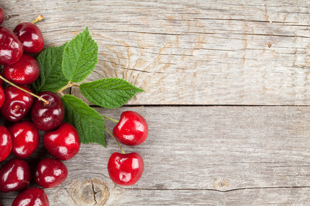 Ripe cherries on wooden table with copy space