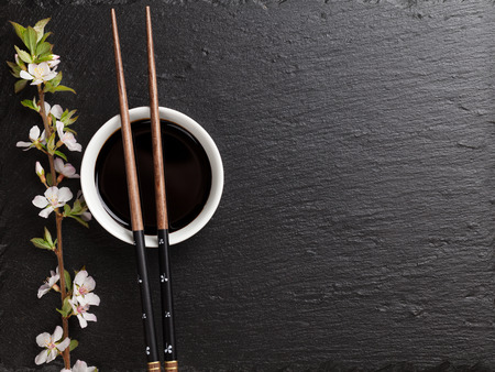 Japanese sushi chopsticks, soy sauce bowl and sakura blossom on black stone background. Top view with copy space Foto de archivo