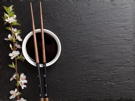 japones bambu: Palillos de sushi japonés, soja bowl salsa y flor de sakura en negro el fondo de piedra. Vista superior con espacio de copia Foto de archivo