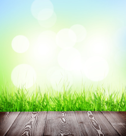 Summer background with wooden floor, green grass and sunlight bokeh photo