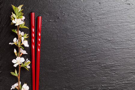 sushi chopsticks: Japanese sushi chopsticks and sakura blossom on black stone background. Top view with copy space