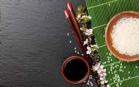 Japanese sushi chopsticks, soy sauce bowl, rice and sakura blossom on black stone background. Top view with copy space photo