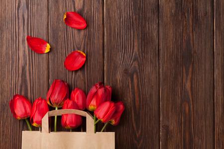 tulipan: Czerwone tulipany bukiet w papierowej torbie na drewnianym stole tle z miejsca kopiowania Zdjęcie Seryjne