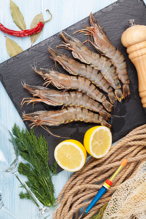 Fresh raw tiger prawns and fishing equipment on wooden table. Top view photo