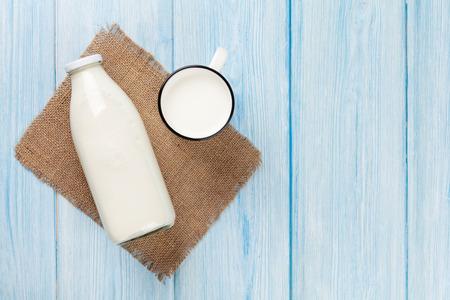 Melk beker en fles op blauwe houten tafel. Bovenaanzicht met een kopie ruimte