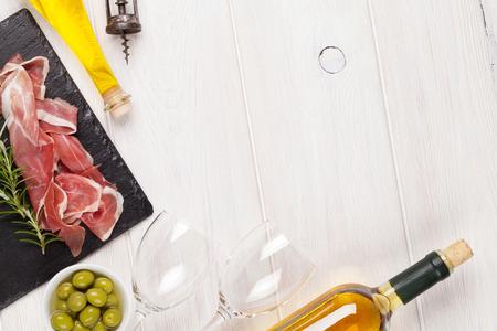 copa de vino: Prosciutto, vino, aceitunas y aceite de oliva en la mesa de madera. Vista superior con espacio de copia Foto de archivo