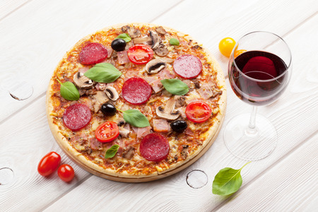Italian pizza with pepperoni, tomatoes, olives, basil and red wine on wooden table. Top view