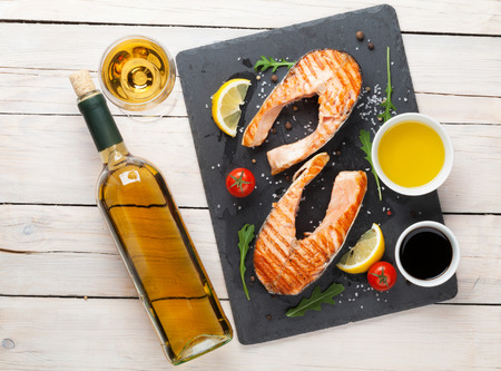 food fish: Grilled salmon and white wine on wooden table. Top view