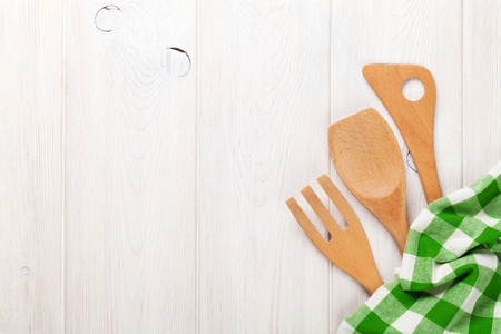 Kitchen utensils over white wooden table background. View from above with copy space