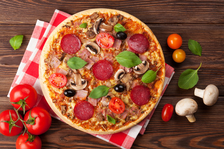 Italian pizza with pepperoni, tomatoes, olives and basil on wooden table. Top view