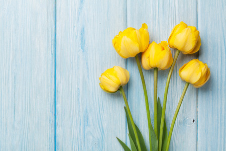 yellow blossom: Yellow tulips over wooden table background with copy space