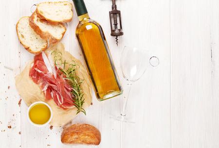 Prosciutto, wijn, ciabatta, parmezaanse kaas en olijfolie op houten tafel. Bovenaanzicht met een kopie ruimte
